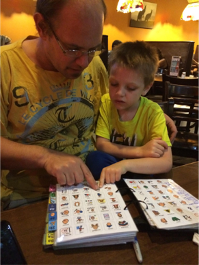 Jason and his son Eddie practicing using Eli's PODD book